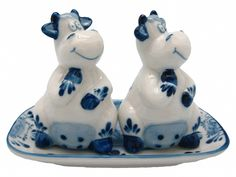 This charming ceramic delft blue salt and pepper shaker set will add a welcome accent to your kitchen or pepper and salt set collection. This set features a charming pair of happy cows on a ceramic pl