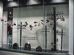 escaparate con un tendido electrico, donde cuelgan pares de zapatillas. colores blanco y negro.  Alejandro Estevez