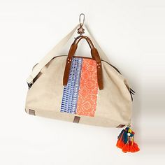 Anthropologie Seville blue, white, and peach embroidered weekender with colorful pom poms.  #rankandstyle http://www.rankandstyle.com/top-10-list/best-july-4th-fashion/anthropologie-seville-embroidered-weekender/