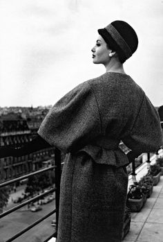 1963 Katherine Pastrie in grey flannel suit with the jacket's belted waist accentuating the full sleeves, cloche in black felt with grey flannel band, Crahay for Nina Ricci
