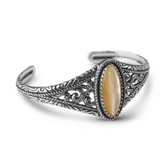 Liven up your wardrobe with rich, warm tones in this American West cuff bracelet. Warm gold mother of pearl shines among oxidized openwork sterling silver adorned with rope and saddle patterns.