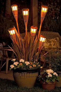 Dollar tree tiki torch solar lights in planter bases.  Great idea for the deck this summer.