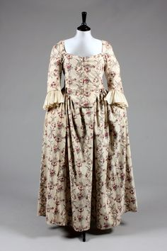 * Printed cotton 'Indienne' robe, French, the fabric 1770s but altered into a closed-robe circa 1780-90, the block printed cotton with vertical bands of baskets of fruits, roses and ribbons in shades of red, blue and brown, with closed-front bodice, the waist cut high at the back, the skirt panels stitched closed at the centre front and with apron-like fall with ties to fasten.