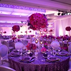 Sequin-embellished linens were topped with fuchsia roses and exotic orchids.