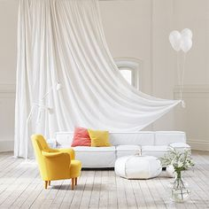I love the long white curtains and the use of the yellow chairs as a contrast