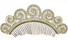 A faux pearl and paste frontlet, circa 1820. Designed as a series of graduating gilt metal scrolls, each set with an outer row of circular-cut colourless paste, with an interior row of faux pearls, above a demilune border of similarly-cut colourless paste, joined to a shaped frame and back comb, width approximately 20cm