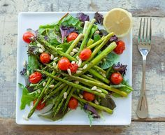 1 bunch of asparagus, ends trimmed 2 cups cherry tomatoes 8 cups mixed greens 2 tbsp pine nuts 1 lemon 1 tsp olive oil (optional) 1/4 tsp sea salt (optional)