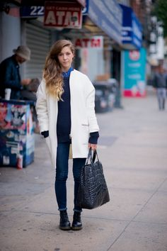 The proportions and the details: tightly rolled dark skinnies to show the laces of her worn in Doc Martens, oversized croc bag - hers is YSL, blue on blue under her coat finished with a cute buttoned up shirt collar peeking out. Details matter: tweaked rolled jeans and adding a collared shirt under a knit.   The slouchy ivory coat is a good contrast piece year round.  Notice the rolled sleeves so her knit peaks out underneath? @wheredidugetthat