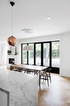 Kitchen with wood floors and a rose gold pendant light