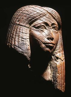 EGYPTIAN WOODEN HEAD OF AN IMPORTANT EGYPTIAN NOBLEWOMAN LATE DYNASTY XVIII/EARLY DYNASTY XIX, CIRCA 1300 B.C. Wearing a tripartite wig, with central parting and finely striated braids, with a serene expression and sensitively modelled eyebrows, eye-line and pupils, on velvet mount 5½ in. (14 cm.) high