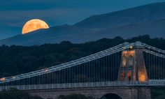 'Blood-Moon Rising'  Menai Bridge, Anglesey. Early shot from the moonrise of the blood/harvest moon on Sept 27th 2015 the night of the lunar eclipse, as the moon began to rise from behind the Carneddau mountains of Snowdonia beyond the Menai Suspension Bridge. Menai Bridge, Wales, United Kingdom.