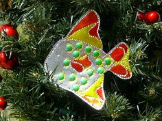 Punched tin tropical fish created in the spirit of the lovely tin tree ornaments made in Mexico.  Sharpies add great color and tiny self sticking colored dots have stayed on his body for 6 years!!!  More: http://gingerbreadsnowflakes.com/node/68