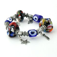 A stunning elasticated bracelet finished with three large multi-colored glass ornaments, several silver charms and three dark blue Evil Eye glass beads.