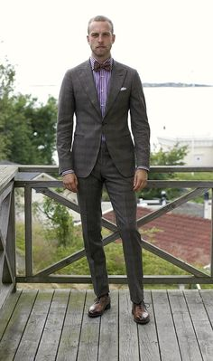 A higher waisted pant and high button make him look quite tall. The purple shirt and bow tie are playful touches.