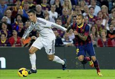 Dani Alves (d), del FC Barcelona, intenta rematar ante la oposición de Cristiano Ronaldo (i), del Real Madrid, durante el partido de Liga