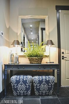 beautiful entryway by the garage door. Love the stools under the entry table, makes so much sense to sit and put on your shoes