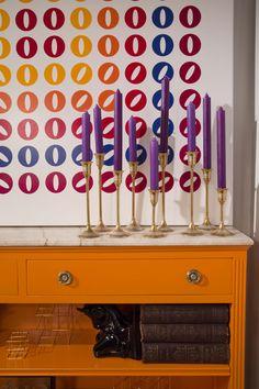 Biblioteca estilo francés laqueado color naraja hernes, candelabros de bronce con velas violetas y el cuadro de circulos de colores de la artista Cristina Hauk. Todo de SALAZAR casa. ESTILO PILAR 2015 BOUQUET