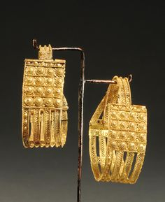ETRUSCAN GOLD FILIGREE EARRINGS  Openwork ribbons filled with wire bands, bosses, scrolls. Probably from Vetulonia  Ca. 1st 1/4 of the 7th Century BC  Dia. 1 9/16 in. (4 cm.) Weight 4.1 gms., 4.3 gms.  Ex Thane Collection, England.  Published: J. Eisenberg, Art of the Ancient World, 1995, no. 131; J. Eisenberg, Art of the Ancient World, 2003, no. 128; J. Eisenberg, Art of the Ancient World, 2011, no. 148.  see: A. Maggiani, ey al., Treasures from Tuscany - The Etruscan Legacy, p. 40, no. 44.
