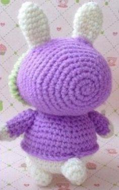 Заяц амигуруми  Очаровательный малыш заяц-амигуруми связан крючком. Заяц одет в плащ лилового цвета с капюшоном на завязках. Плащ обвязан пряжей контрастного салатового цвета. Основное тело зайца связано из пряжи белого цвета. Такого зайца-амигуруми можно использовать в качестве брелка к рюкзаку или сумке. Капюшон имеет отверстие для больших ушей зайчика, его по желанию можно снимать или одевать. Основной узор зайца-амигуруми это столбик без накида. Как связать зайца-амигуруми крючком…