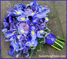Blue, lavender, and green bridal bouquet by Something Floral/Something Spectacular, Warren, MI, features blue irises, lavender roses, periwinkle lilacs, and blue violet French anemones.