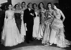 French coutourier Christian Dior stands with his house models wearing gowns of…