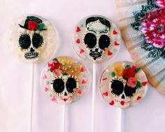 Horchata flavored Mexican sugar skull wedding lollipops. The skulls are made out of hand painted and cut gum paste with black edible glitter eye sockets. They are gorgeously decorated with bright handmade marzipan roses (marzipan is an almond confection and does contain nuts), crowns, and top hats, all dusted with colorful edible glitter and candy dragees. The skulls are floating in candy that's been sprinkled with edible silver glitter and finished off with candy pearls and heart candies.