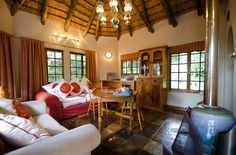 Tucked into the forest, Crowned Eagle Cottage is both modern and warmly decorated in rich reds and oranges. The wooden deck provides a breath-taking view over the forest. This is the territory of a pair of Crowned Eagles – the nest has been in the same spot for at least 70 years and is visible from the cottage. Self Catering Cottages, Wooden Decks, Underfloor Heating, Eagles, Nest, Lounge, Warm, Modern, Design