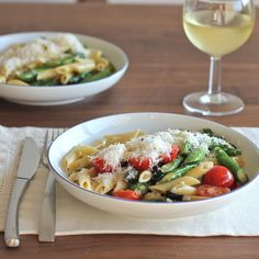 Simple quick and easy weeknight pasta recipe of green asparagus with cherry tomatoes and black olive penne cooked in white wine.