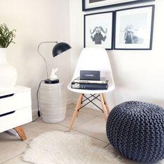 meubles scandinaves dans le salon - chaise Eames blanche, pouf tricot gris, tapis blanc à poils longs et deux tables d'appoint blanches