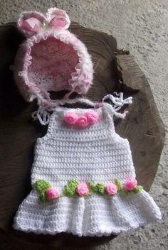 Vestido e gorro confeccionados em fio importado antialérgico.  detalhes - flores de crochê, fitas  cor - branco com detalhes rosa  tamanhos - 1 a 3 / 3 a 6 meses R$ 130,00