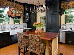 The wood-topped kitchen island, black cabinets and marble backsplash are classic details in this traditional kitchen. The chandelier, paisley window treatments and covered bar stools add an elegant touch.
