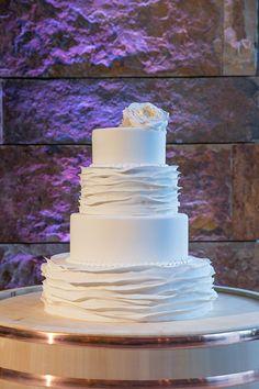 A four-tier, ruffled white wedding cake | Brides.com