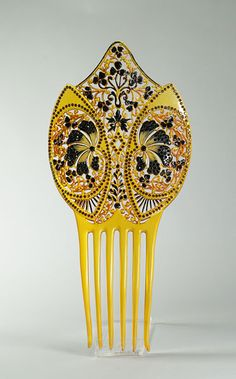 Late 19th century, America - Comb - Curved celluloid comb with floral motifs yellow and black and embellished with black paste stones
