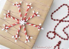 DIY Christmas Gift Wrapping.  Red & white straws with white pipe cleaners, a white button & baker's string.