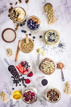 Eight Overnight Oats recipes in glass jars surrounded by lemons, cinnamon sticks, peanut butter, black sesame seeds and oats.
