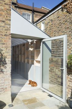 An oversized hinged door creates generous access into the garden and acts as a picture window when closed. An oversized hinged door creates generous access into the garden and acts as a picture window when closed. Garage Extension, Cottage Extension, Side Return Extension, House Extension Design, Extension Designs, Glass Extension, Extension Ideas, Bungalow Extensions, House Extensions