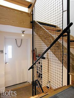 Industrial grade steel tubing and wire mesh netting serve as safety railings throughout the stairwell.
