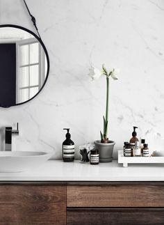 Une salle de bain en marbre blanc et bois vintage au style minimaliste avec orchidée et miroir rond ceinture.