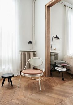 blush chair, parquet floor, black lamp, black stool