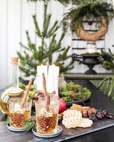 Glöggmys med äppelglögg, klenäter och pepparkakor på glasverandan. Ett stort fat med mossa och vita ljus sprider extra julstämning, liksom tallen i damejeannen.