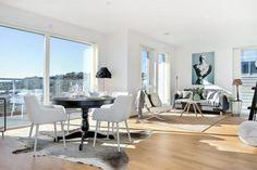 czarny stół okragły na jednej nodze z białymi krzesłami w stylu nowoczesnym,biało-szary dywan z bydlęcej skóry na podłodze w otwartej jadalni