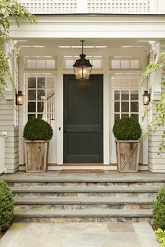 Thornton Designs - home exteriors - portico, portico porch, portico entryway, flagstone, flagstone steps, clipped boxwoods, boxwood planters, sidelights, glass paned sidelights, black front door, transom window, transom window over front door, transom window in entryway, carriage house lantern, carriage house sconce, carriage house lantern sconce, driftwood planter, wooden planter, exterior shingles, tan shingles, shingled exterior,