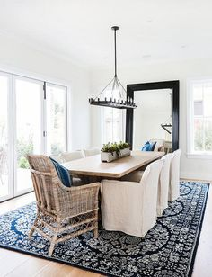 Modern Farmhouse with Transitional Interiors. Dining Room: he dining room features an iron linear chandelier above a reclaimed wood trestle dining table lined with natural linen slipcovered dining chairs and captain wicker chairs. A navy blue and white medallion rug brings color and softness to the space.