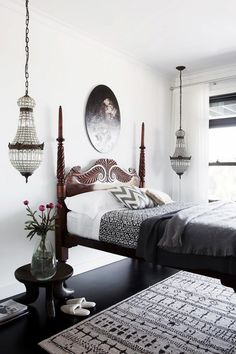 Contemporary bedroom with matching chandeliers, and a vintage headboard