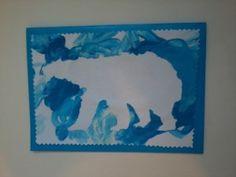Вырезаем силуэт медведя. Немного приклеиваем его на лист белой бумаги. Поверх раскрашиваем белой и синей пальчиковой краской. Осторожно отклеиваем силуэт медведя. Рисунок сохнет. Приклеиваем его на фон синего цвета. Предварительно раскрашенный лист можно обработать фигурными ножницами.