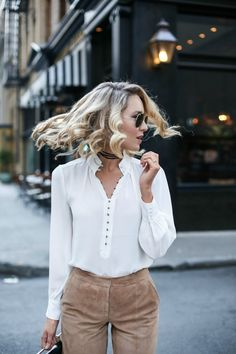 curled hairstyle white blouse suede camel pants
