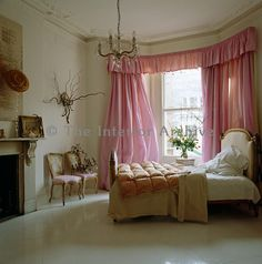 The bay window of this lovely feminine bedroom in an apartment in west London is dressed in a set of pink silk curtains