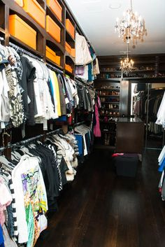 Tina Craig's dark wood closet has open shelves that hold orange Hermes boxes