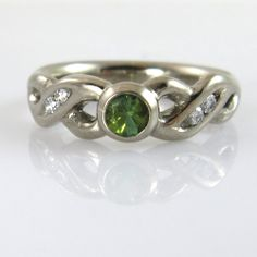 """Celtic inspired engagement ring. """"She said yes"""" the joyous mail informed me, and my day got even better. I so love, when my customers share their happiness with me and this time, a ring, based on his design, carefully thought out just for her, was part of it. The ring was carved from 14k white gold, held a juicy green tourmaline and was flanked by a total of 0,08 carat TW/VVS diamonds. I would have said yes too ;-)"""