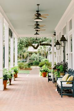 Classic and elegant Charleston, SC southern-style porch with fans on the painted blue ceiling.